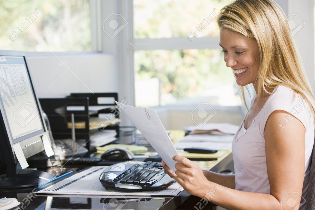 Woman in home office with computer and paperwork smiling Stock Photo - 3485599