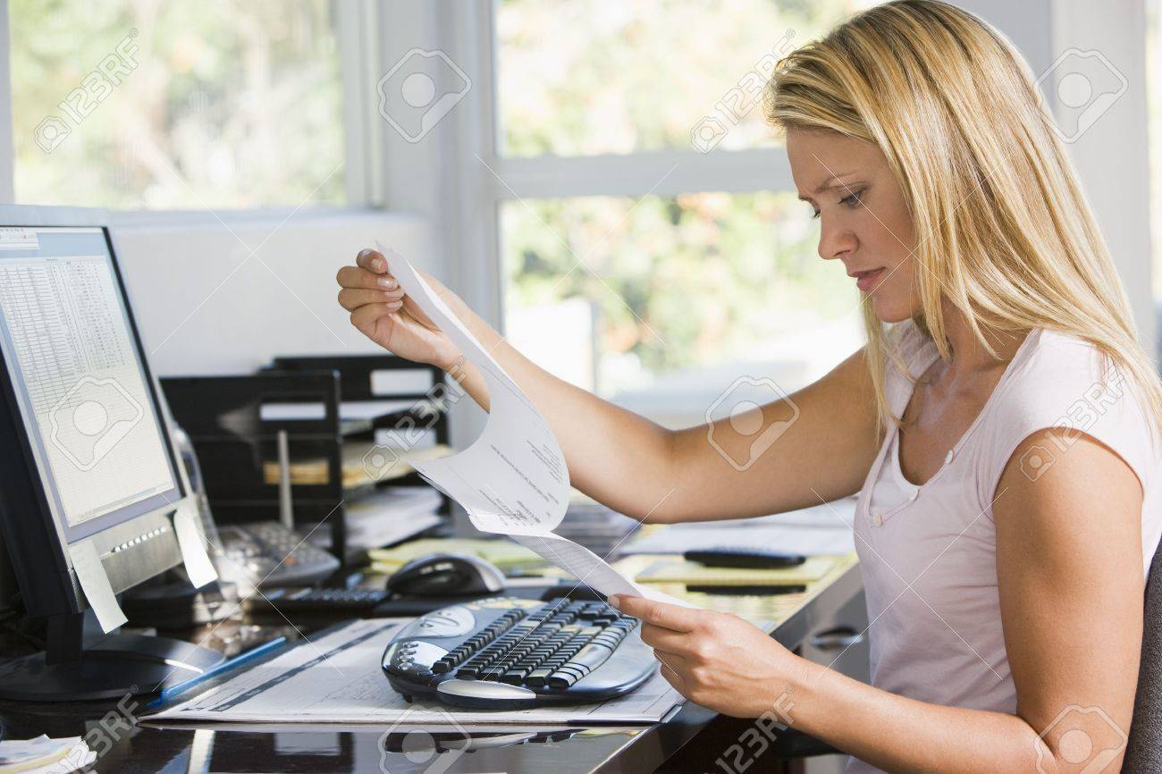 Woman in home office with computer and paperwork frowning Stock Photo - 3485683