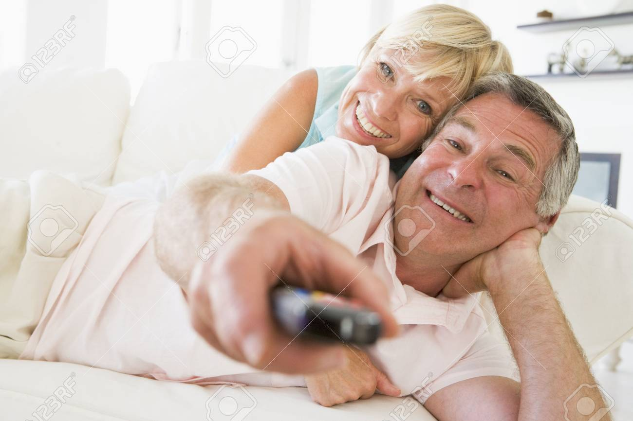 Couple in living room using remote control smiling Stock Photo - 3485127