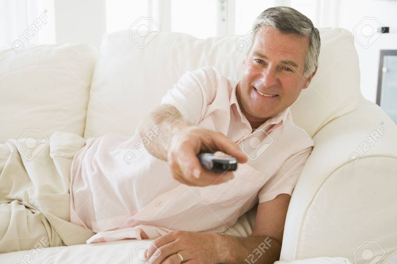Man in living room using remote control smiling Stock Photo - 3483093
