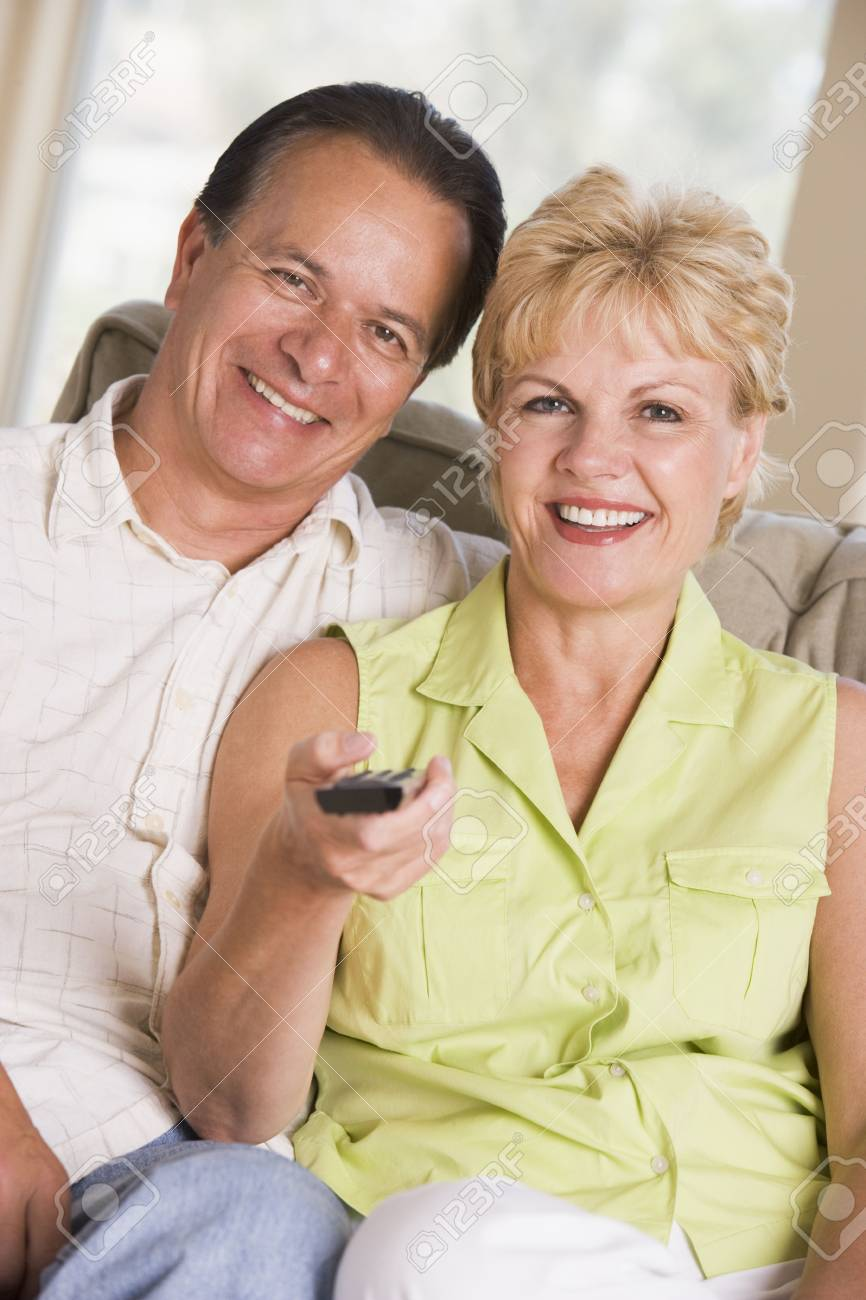 Couple in living room using remote control smiling Stock Photo - 3485303