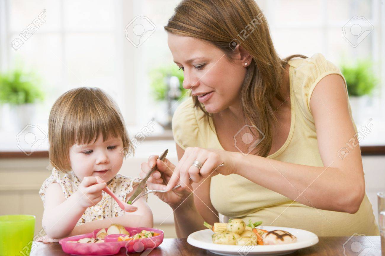 Pregnant mother in kitchen eating chicken and vegetables helping daughter eat Stock Photo - 3486375