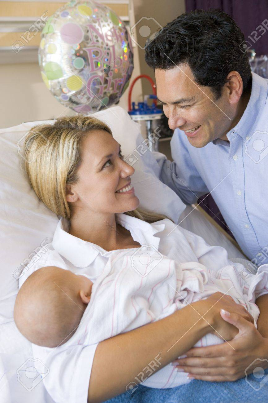 New mother with baby and husband in hospital smiling Stock Photo - 3487198
