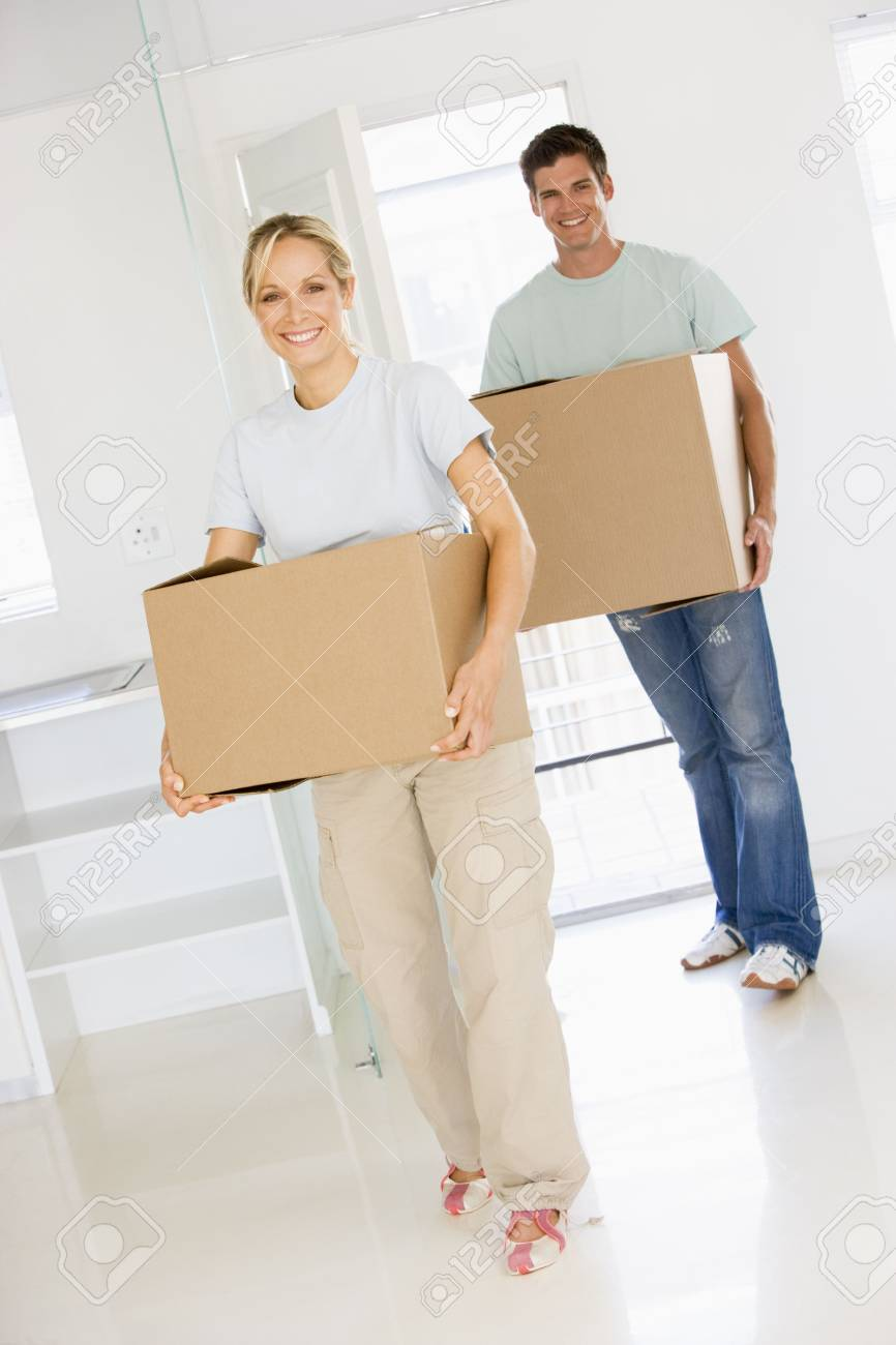 Couple with boxes moving into new home smiling Stock Photo - 3485812