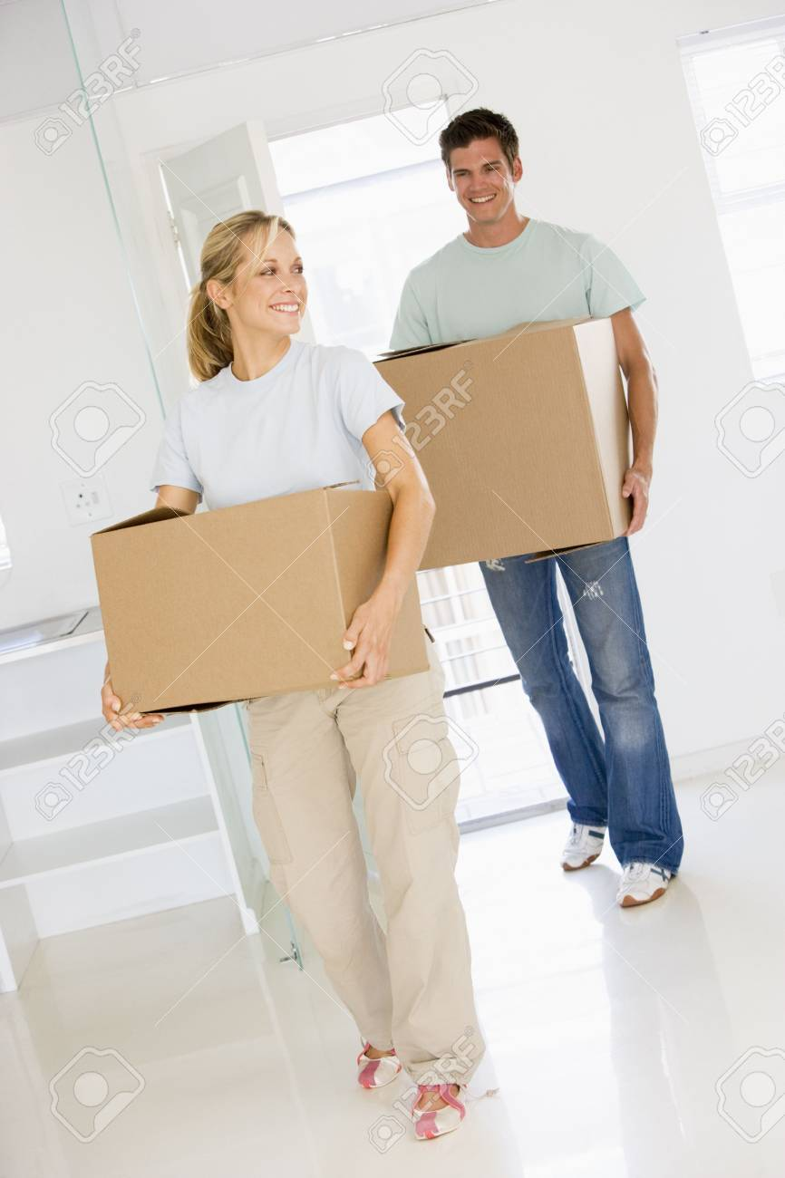Couple with boxes moving into new home smiling Stock Photo - 3486188