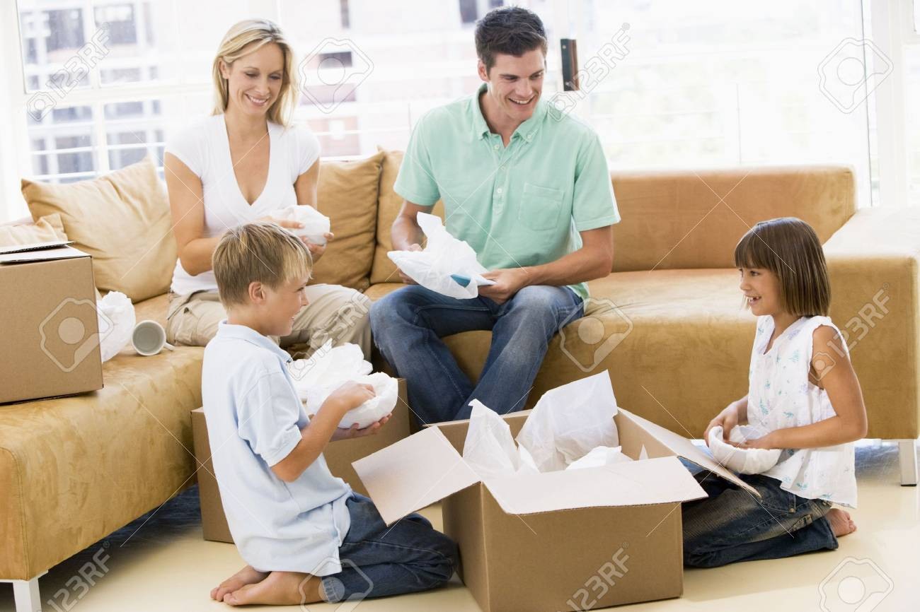 Family unpacking boxes in new home smiling Stock Photo - 3487219