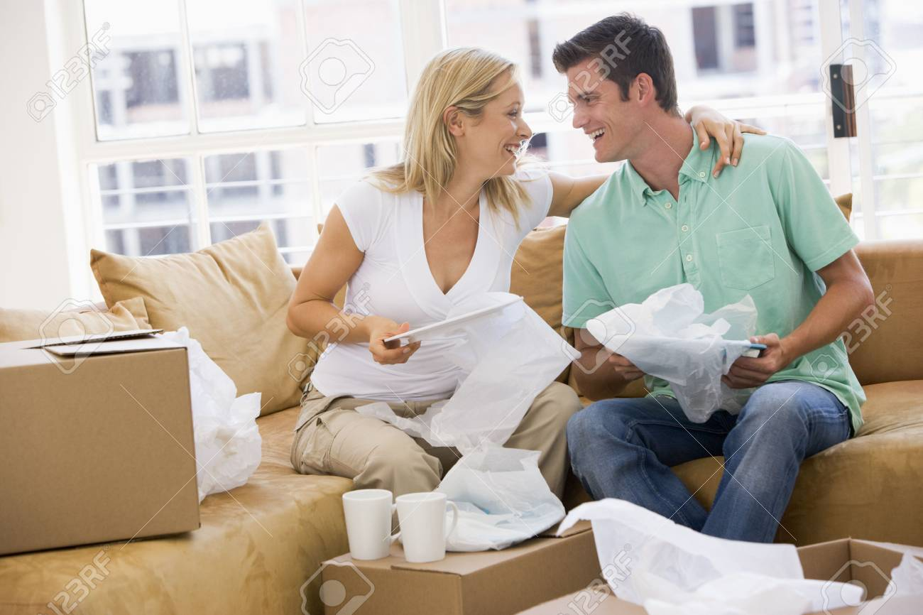 Couple unpacking boxes in new home smiling Stock Photo - 3486982