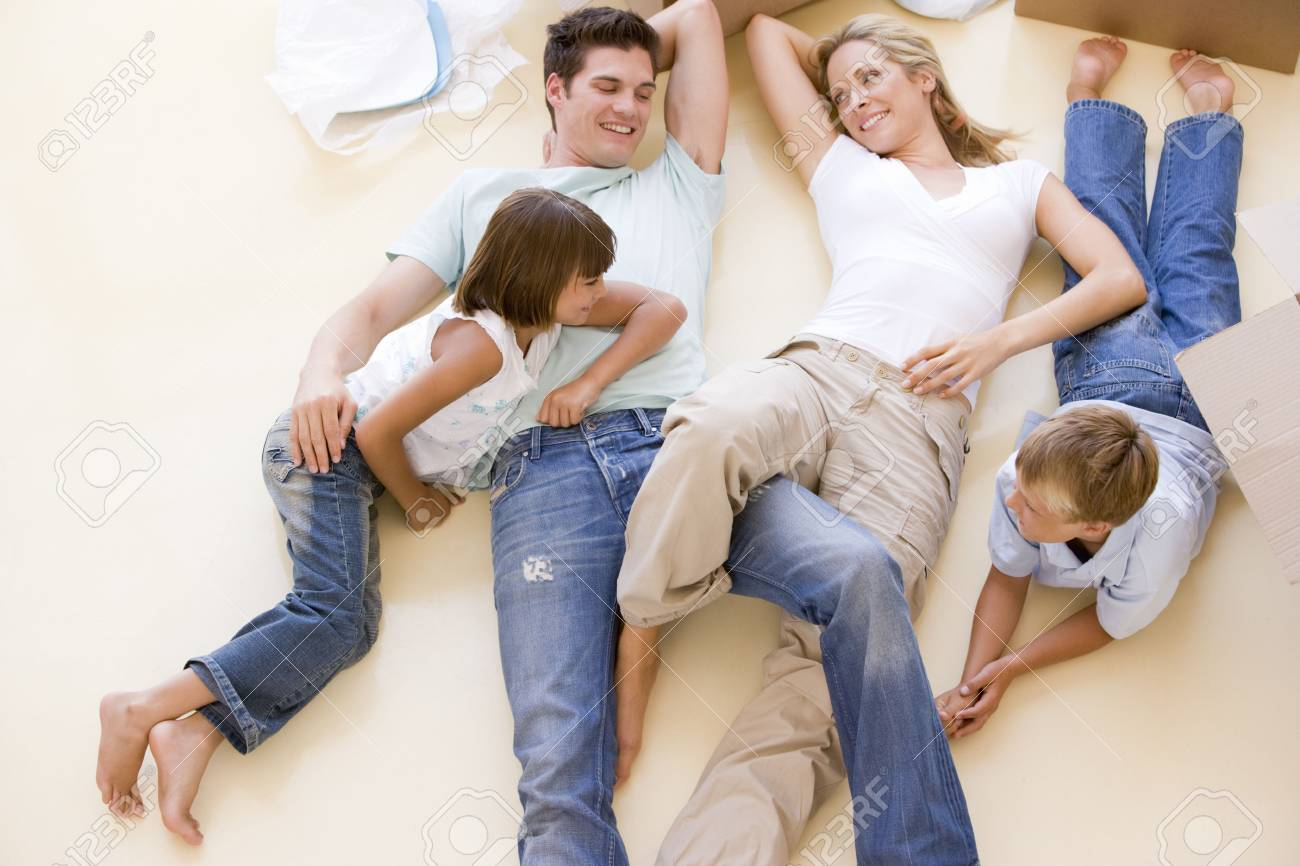 Family lying on floor by open boxes in new home smiling Stock Photo - 3487164