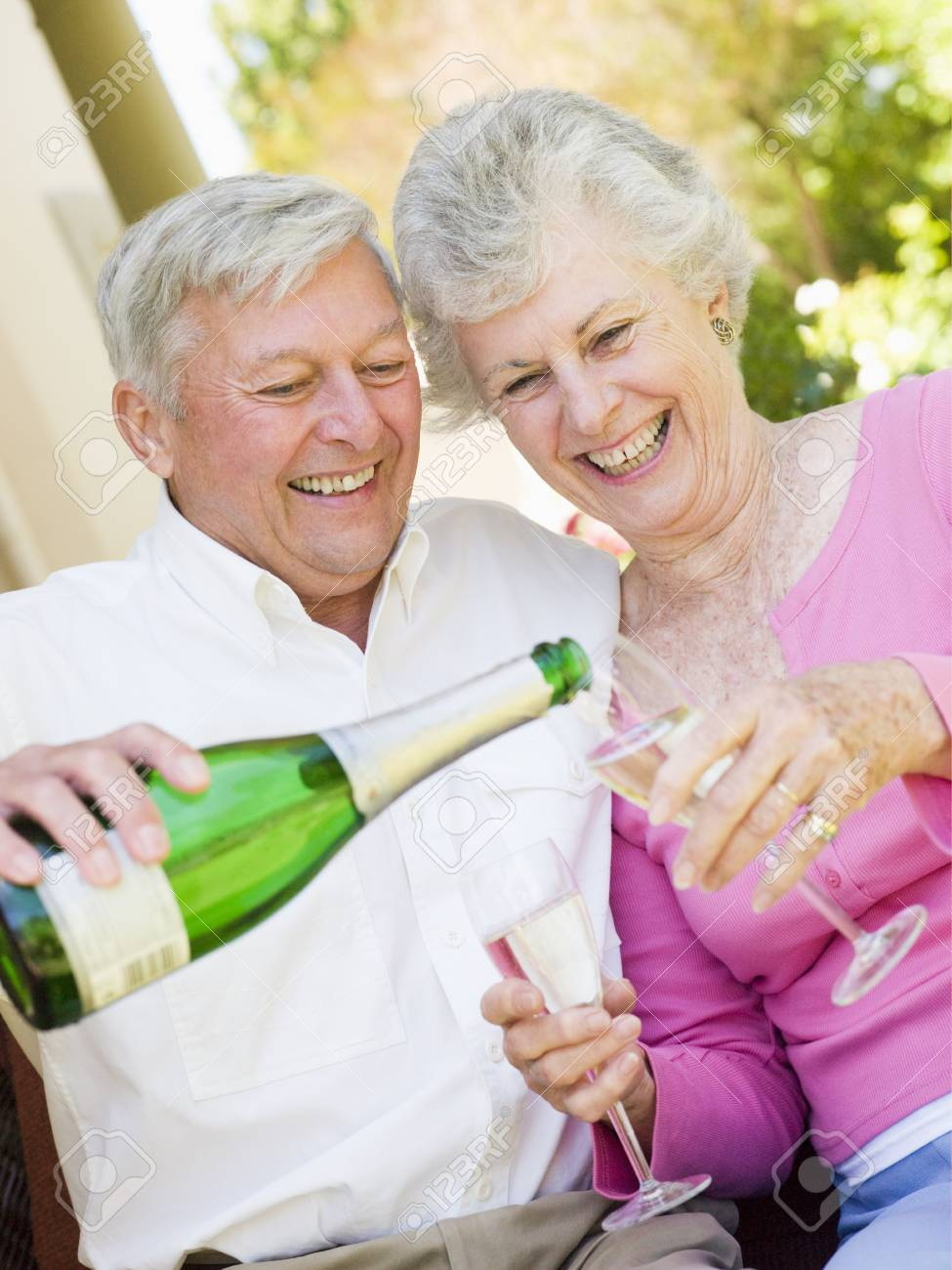 Couple on patio drinking champagne and smiling Stock Photo - 3488213