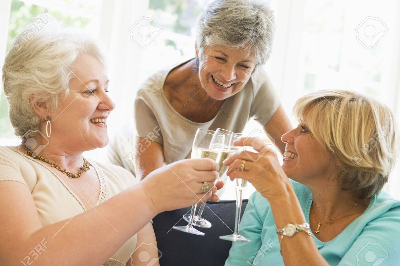 Three women in living room toasting champagne and smiling Stock Photo - 3487168