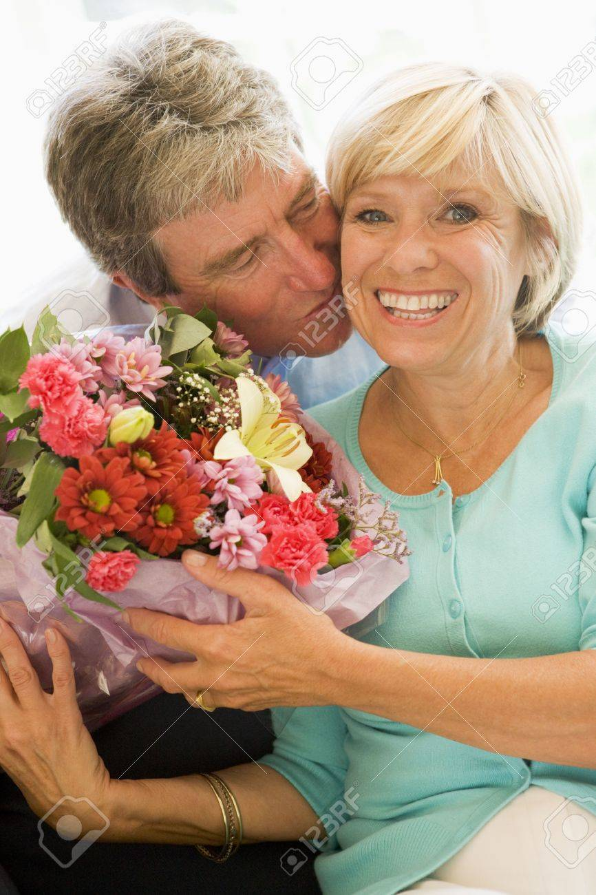 Husband giving wife flowers kissing and smiling Stock Photo - 3487921