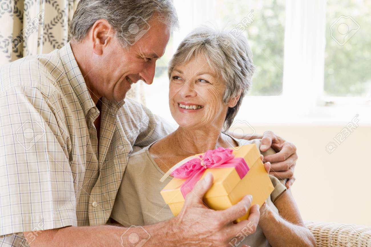 Husband giving wife gift in living room smiling Stock Photo - 3488052