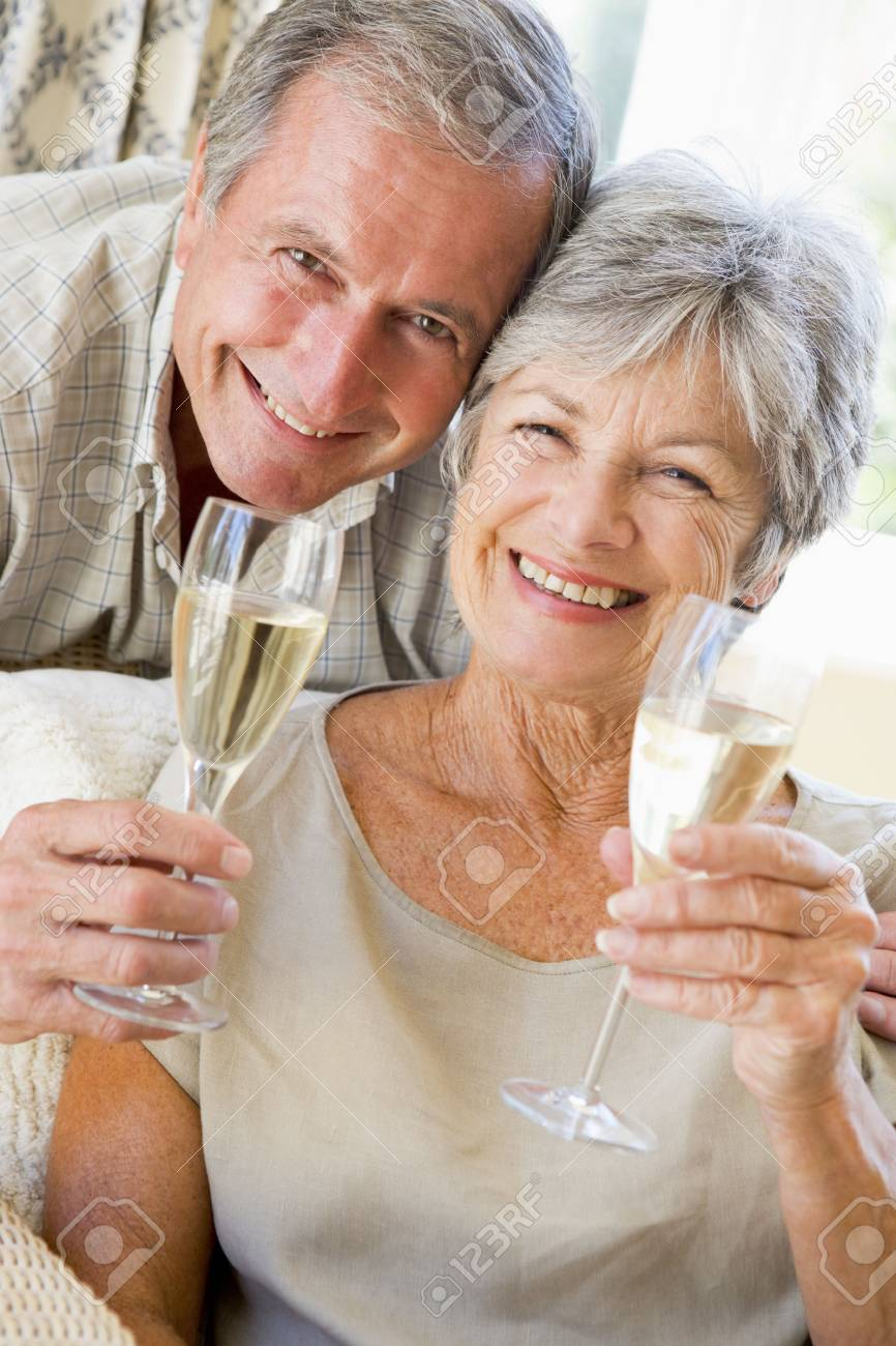 Couple in living room drinking champagne and smiling Stock Photo - 3487925