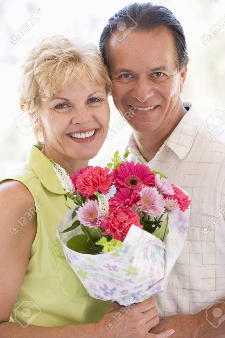 Husband and wife holding flowers and smiling Stock Photo - 3488049