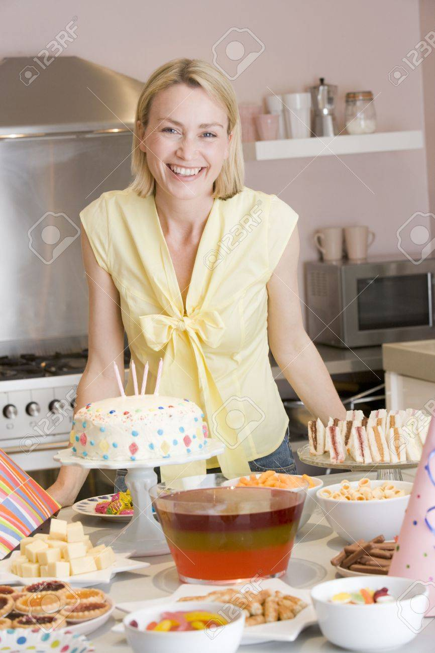 Woman at party standing by food table smiling Stock Photo - 3486730