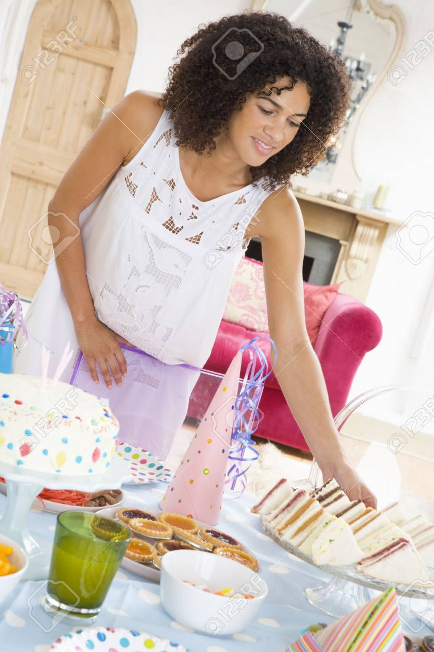 Woman at party getting sandwich from food table smiling Stock Photo - 3486993