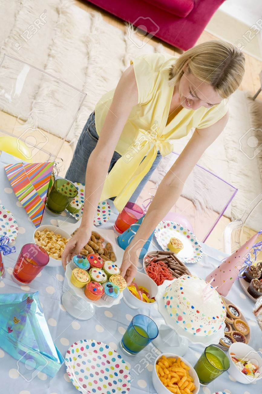 Woman at party setting out food and smiling Stock Photo - 3488003