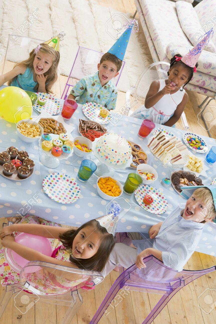 Young children at party sitting at table with food smiling Stock Photo - 3488169