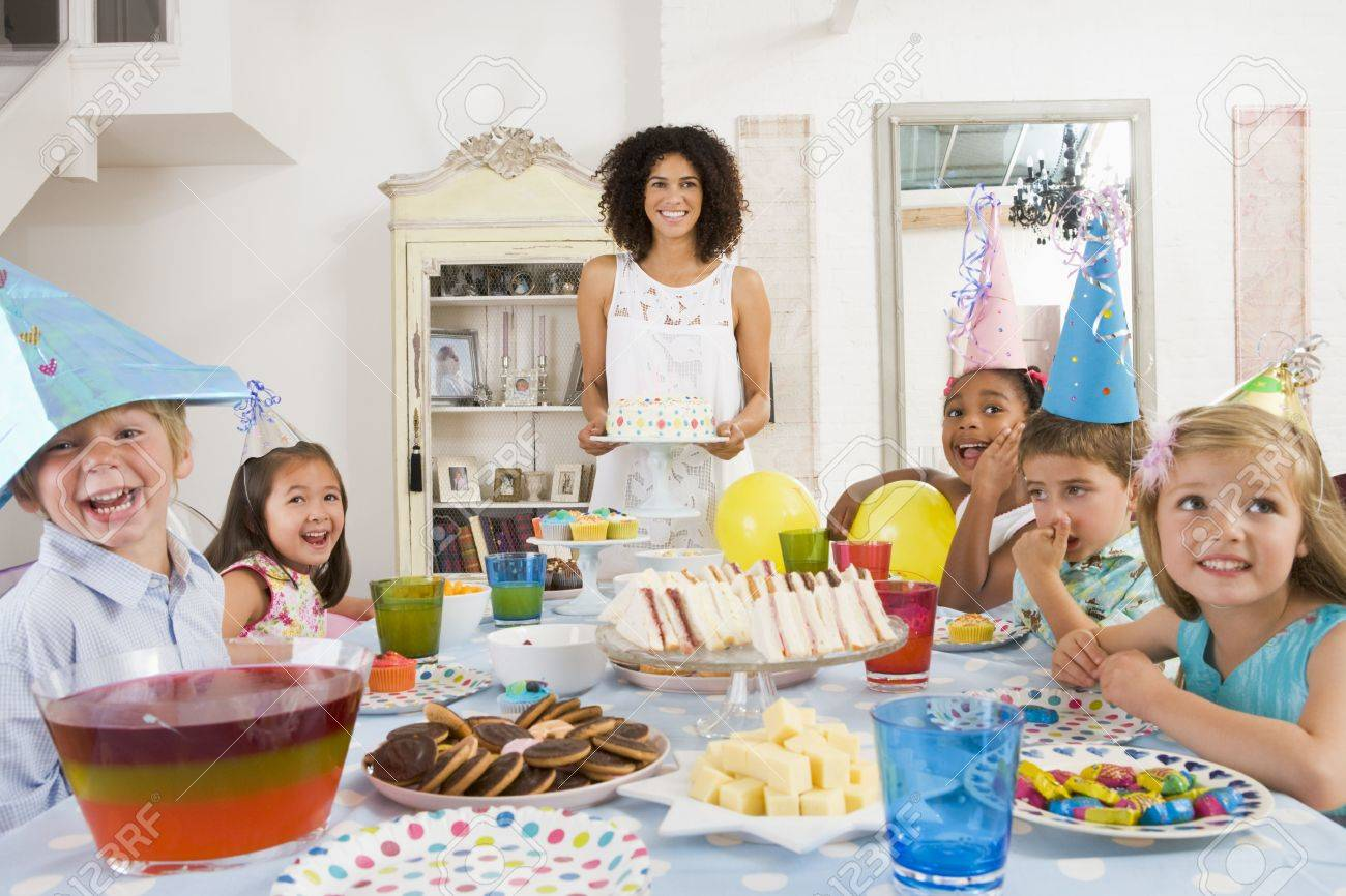 Young children at party sitting at table with mother carrying cake and smiling Stock Photo - 3487227