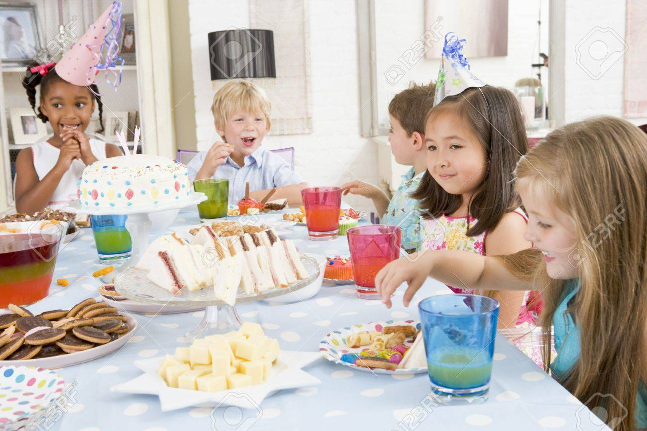 Young children at party sitting at table with food smiling Stock Photo - 3487161