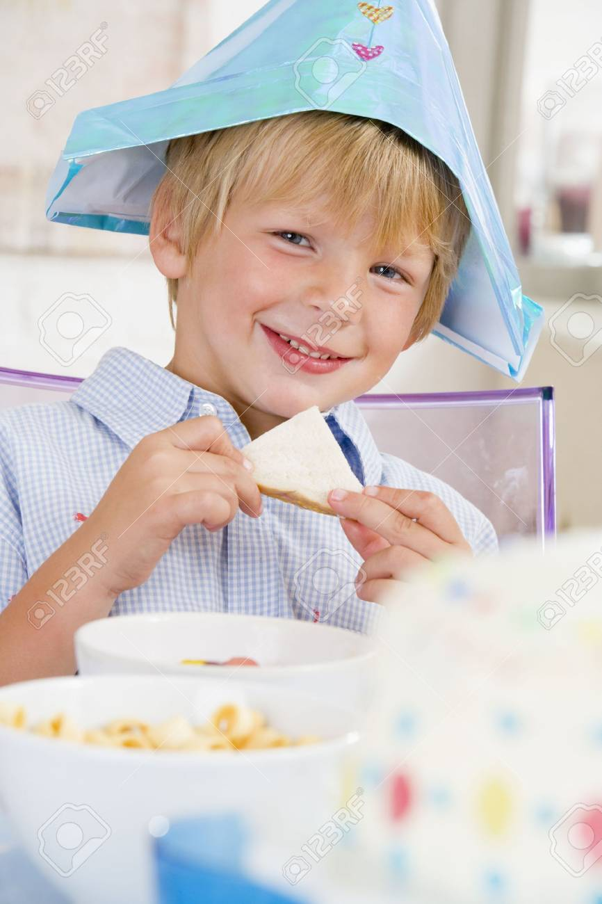 Young boy at party sitting at table with a sandwich smiling Stock Photo - 3486296