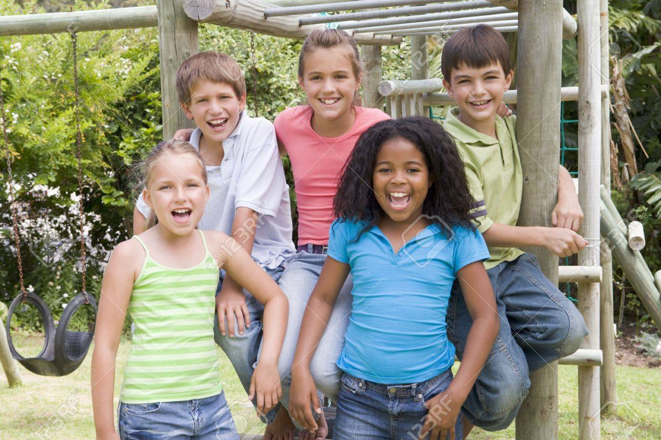 Five young friends at a playground smiling - 3488231
