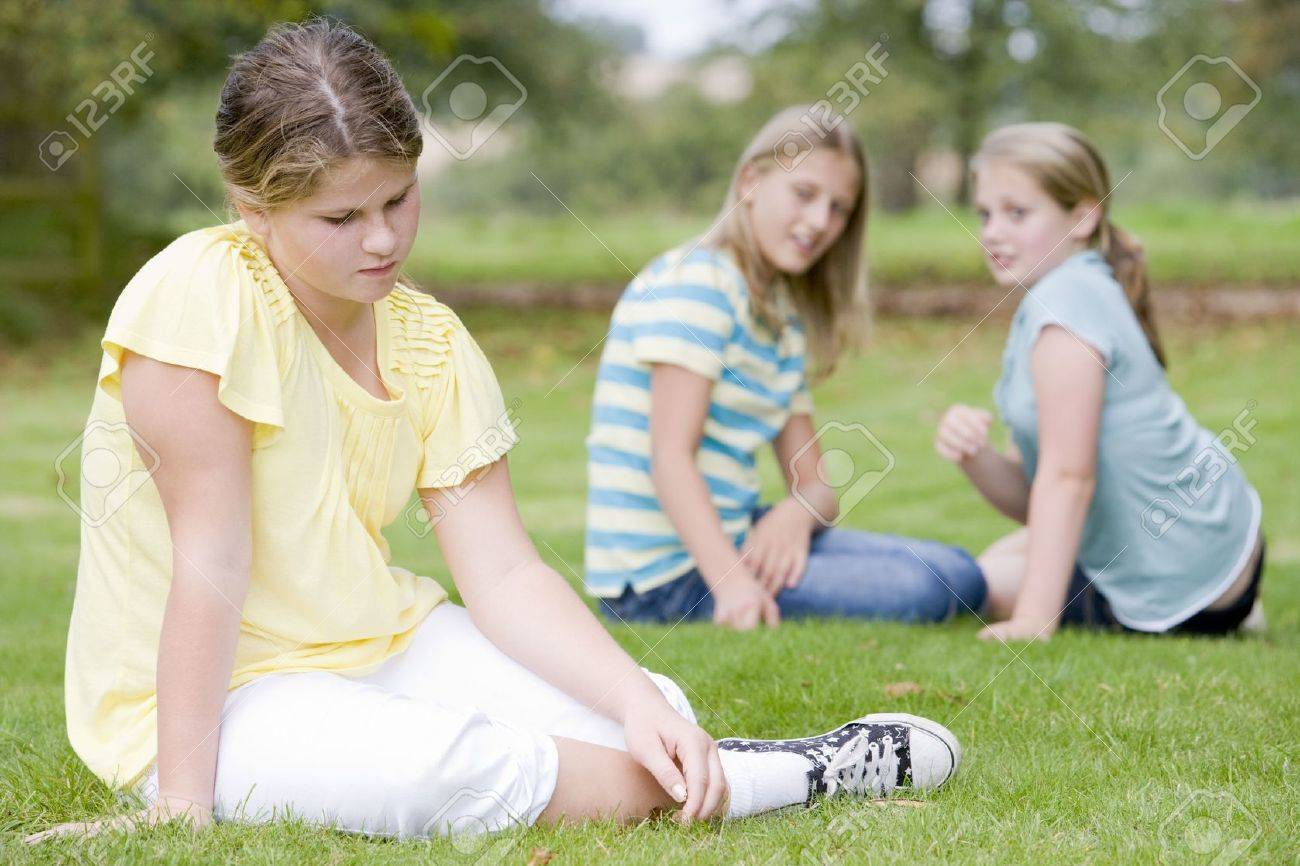 Two young girls bullying other young girl outdoors Stock Photo - 3487206