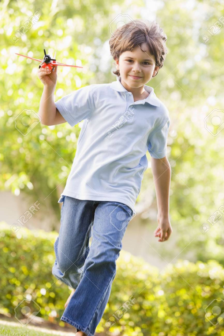 Young boy with toy airplane running outdoors smiling Stock Photo - 3487099