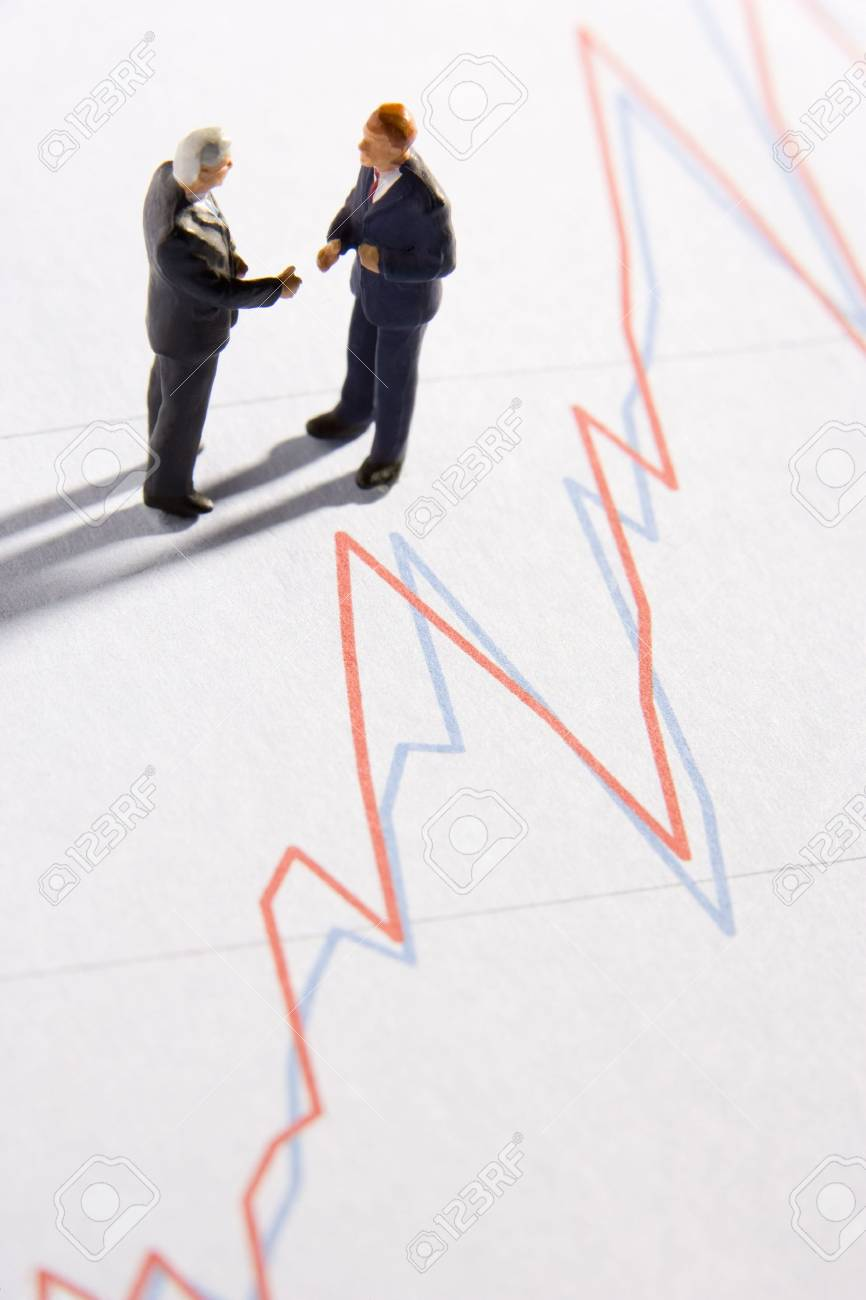 Figurines Of Two Businessmen Shaking Hands On A Line Graph Stock Photo - 3709668