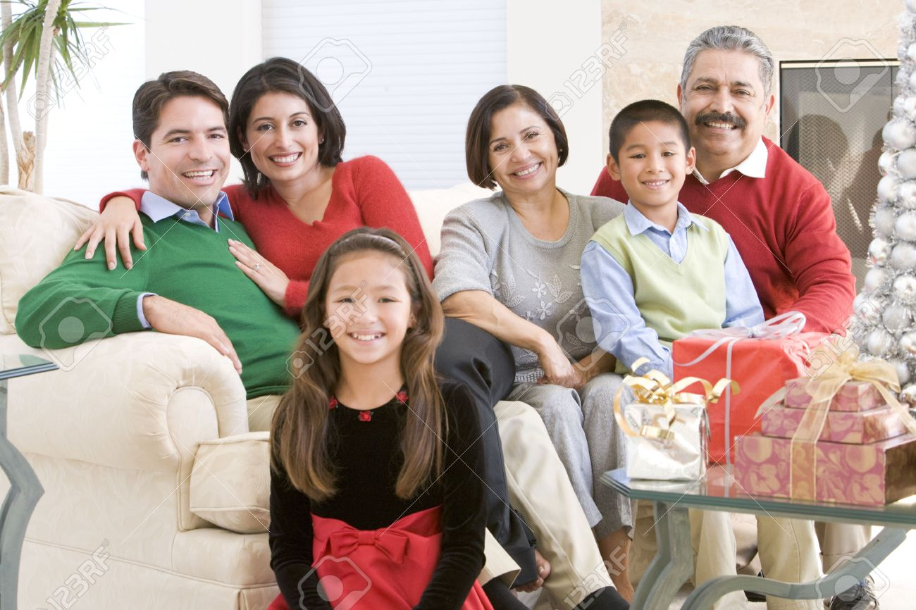 family sitting around a coffee table and christmas gifts stock photo
