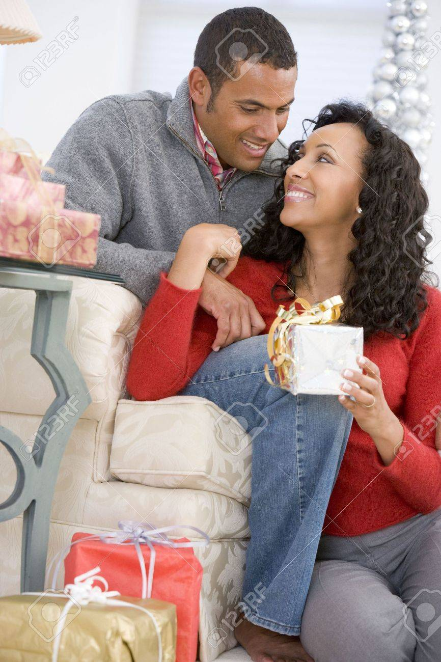 Husband And Wife Affectionately Exchanging Christmas Gifts Stock Photo - 3724953