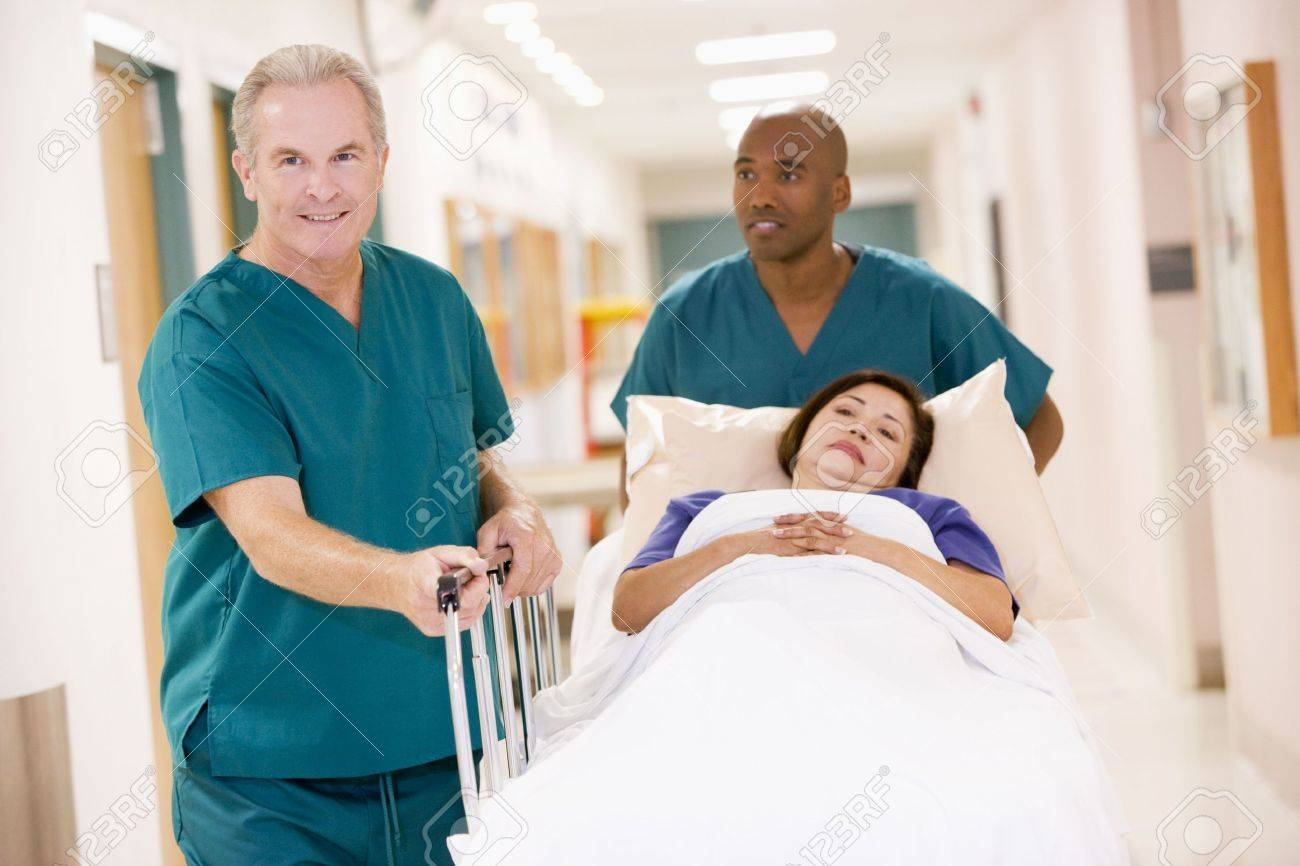 Two Orderlies Pushing A Woman In A Bed Down A Hospital Corridor Stock Photo - 3723780