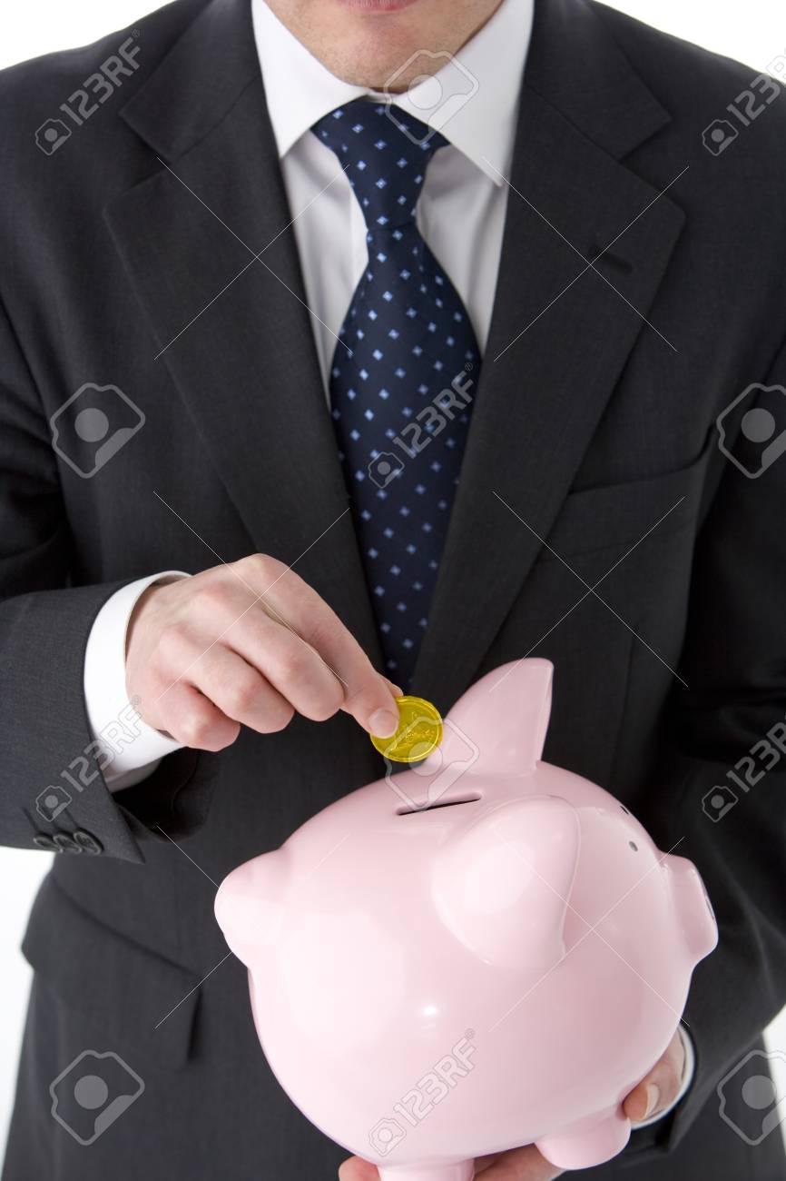 Businessman Putting Coin Into Piggy Bank Stock Photo - 4444736