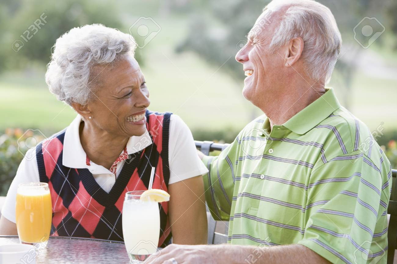 Couple Enjoying A Beverage By A Golf Course Stock Photo - 4506978