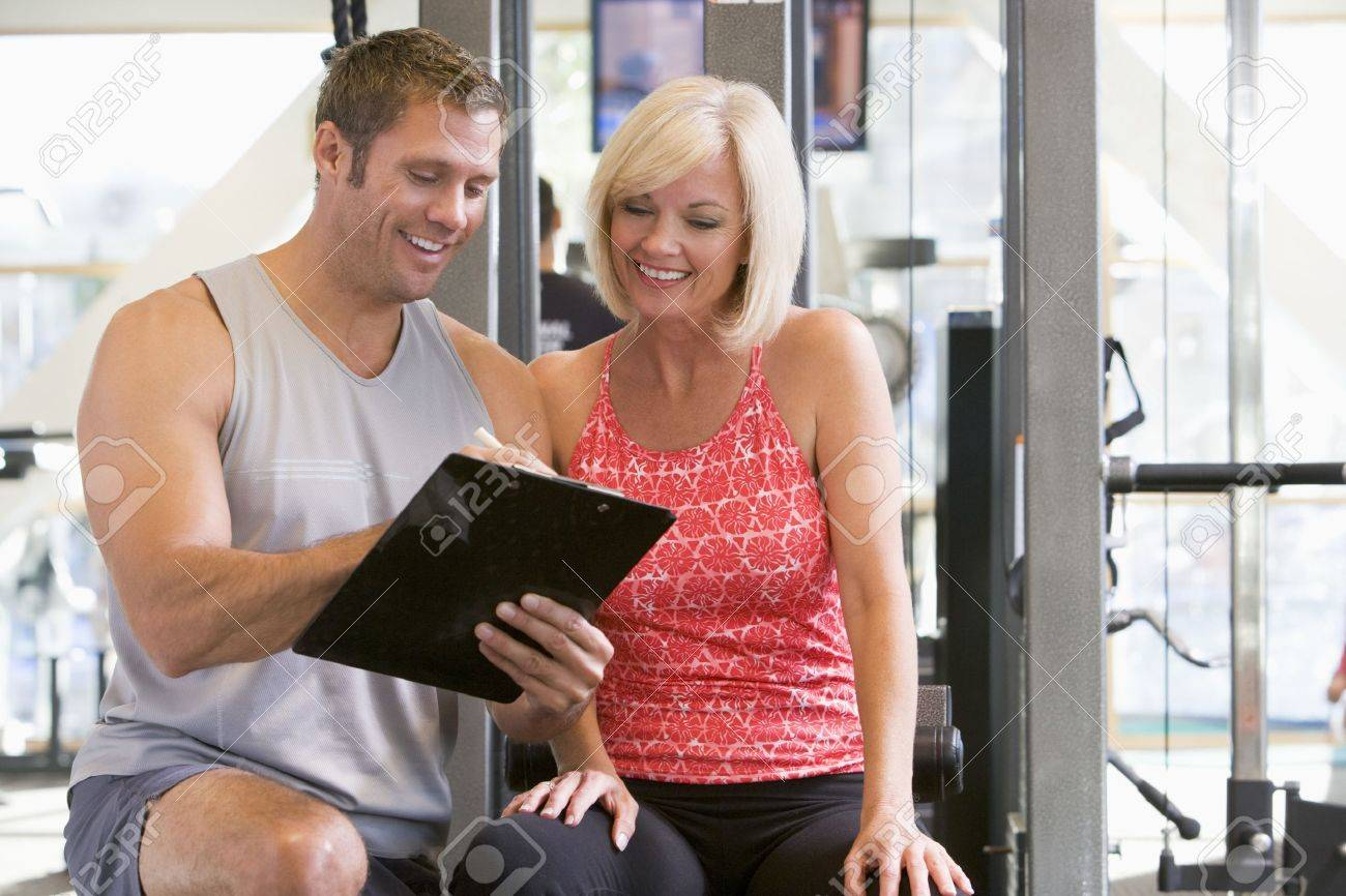 Personal Trainer Talking To Woman At Gym Stock Photo - 4507380