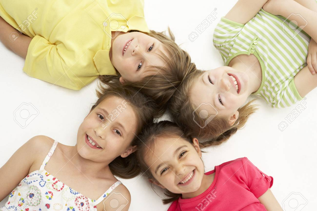 Circle of four young friends lying down smiling Stock Photo - 5631176