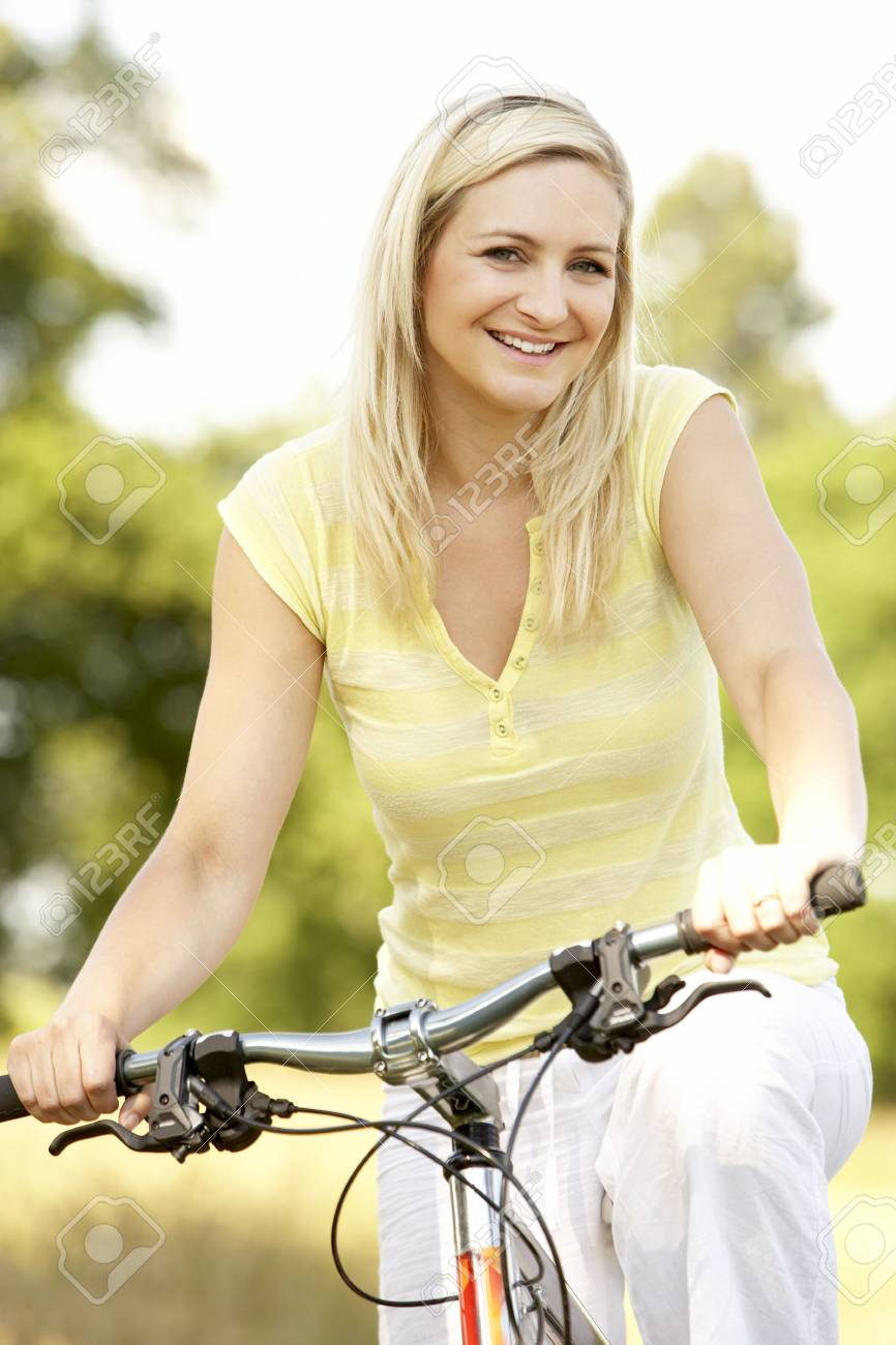 Young woman riding bike in countryside Stock Photo - 5633207