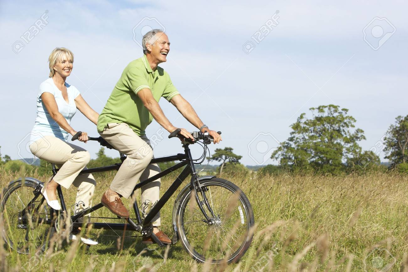 mature couple riding tandem stock photo, picture and royalty free