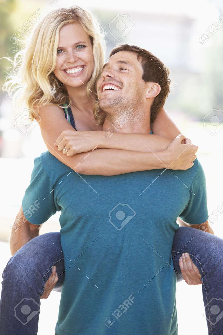 Young Man Giving Woman Piggyback Outdoors Stock Photo - 6143248