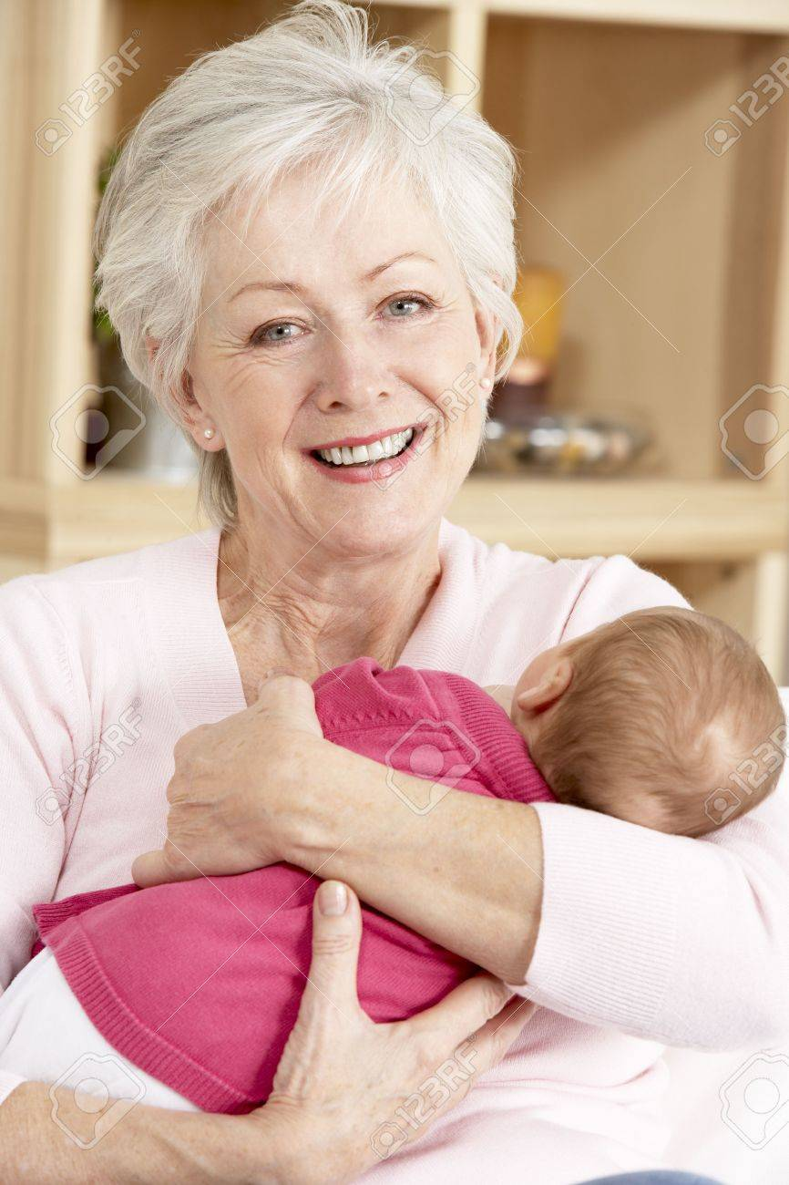 Grandmother Cuddling Granddaughter At Home Stock Photo - 6453046