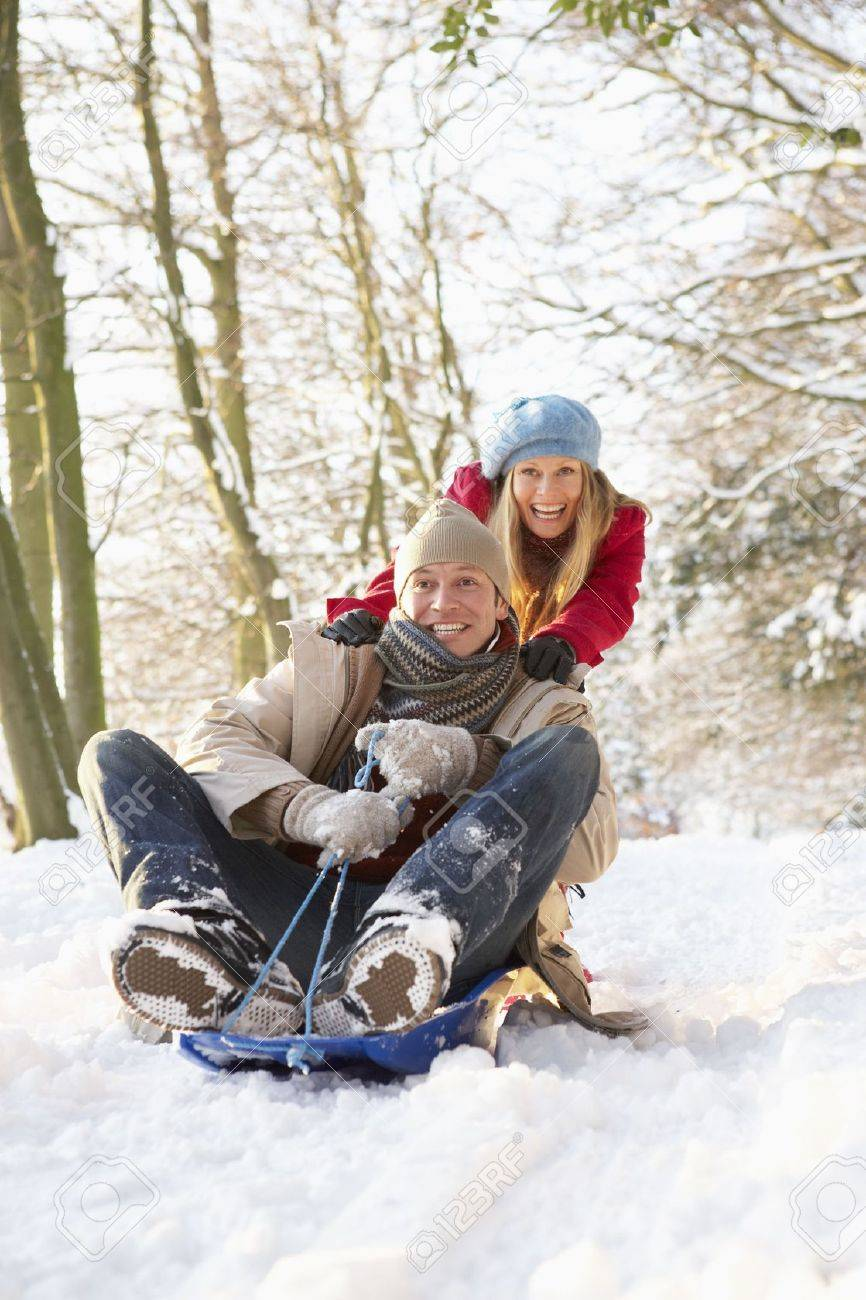 Couple Sledging Through Snowy Woodland Stock Photo - 6450949
