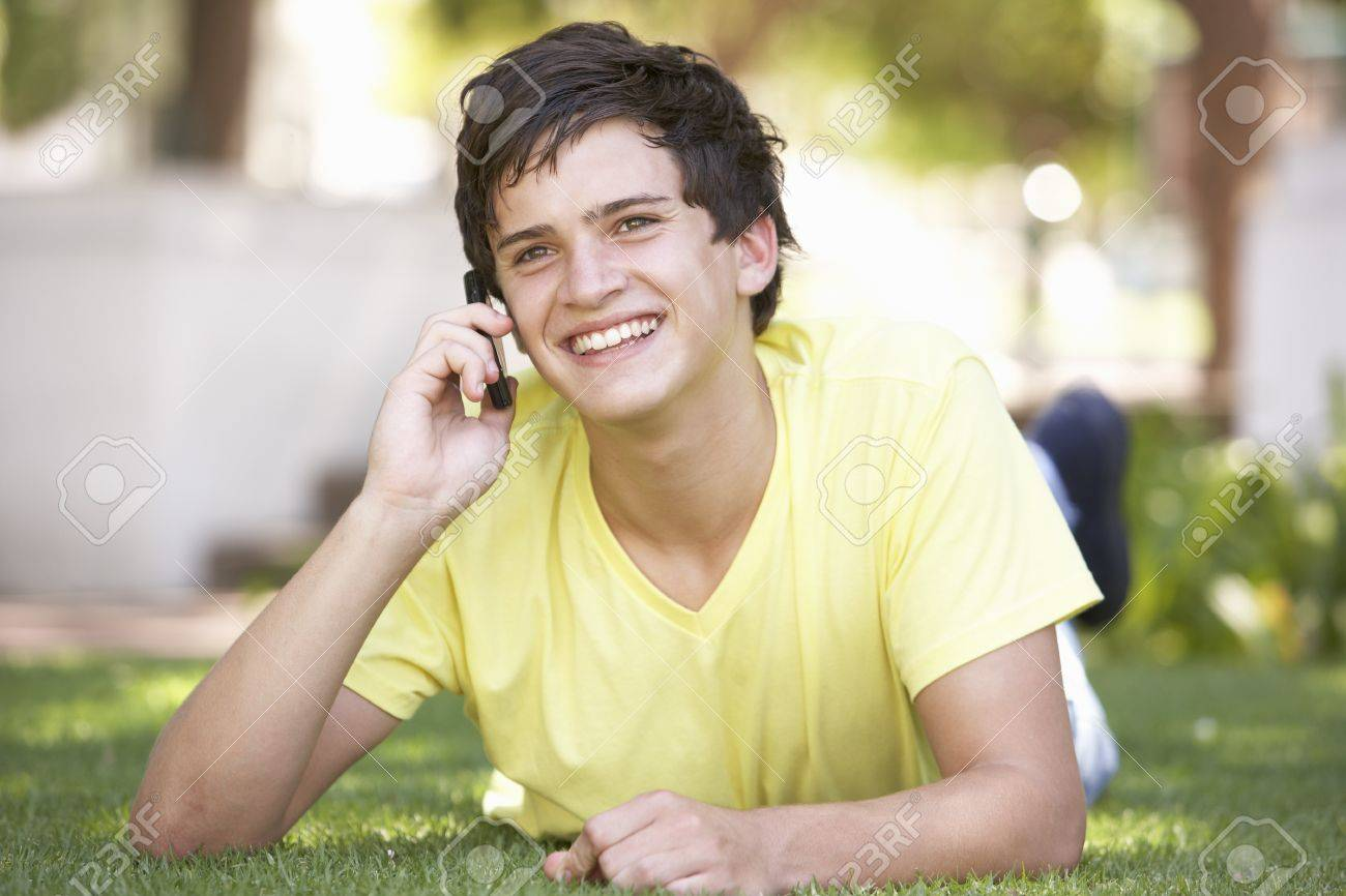 Teenage Boy Laying In Park Using Mobile Phone Stock Photo - 8108542