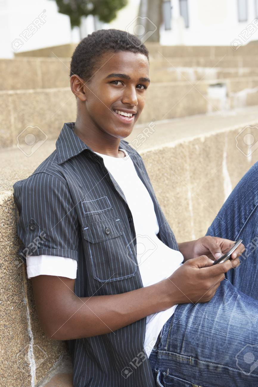 Male Teenage Student Sitting Outside On College Steps Using Mobile Phone Stock Photo - 8108716
