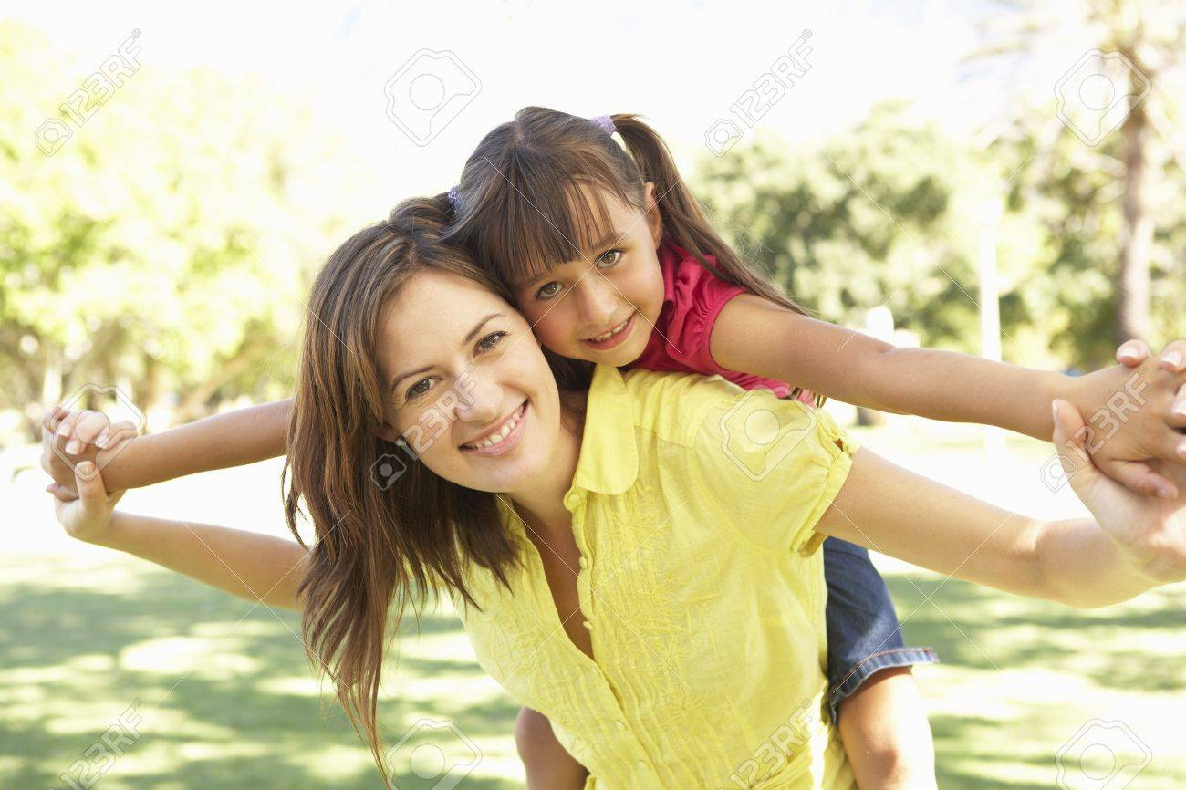 Mother Giving Daughter Ride On Back In Park Stock Photo - 8108559