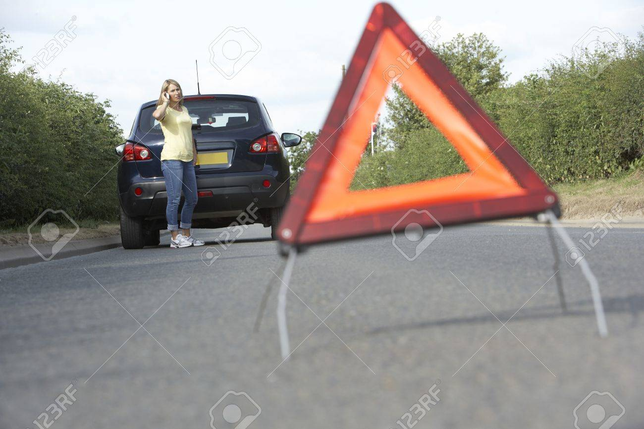 Female Driver Broken Down On Country Road With Hazard Warning Sign In Foreground Stock Photo - 8108877