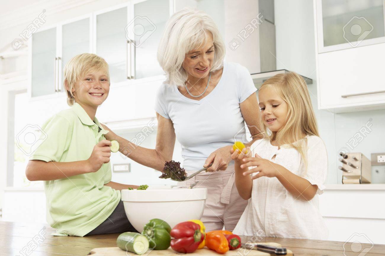 Grandchildren Helping Grandmother To Prepare Salad In Modern Kitchen Stock Photo - 8198645