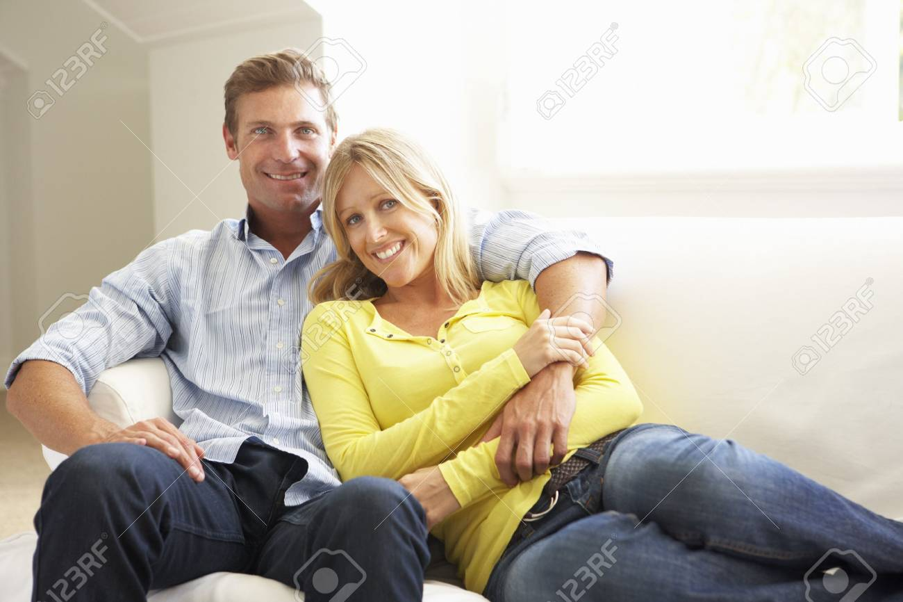 Couple Relaxing On Sofa At Home Stock Photo - 8198761