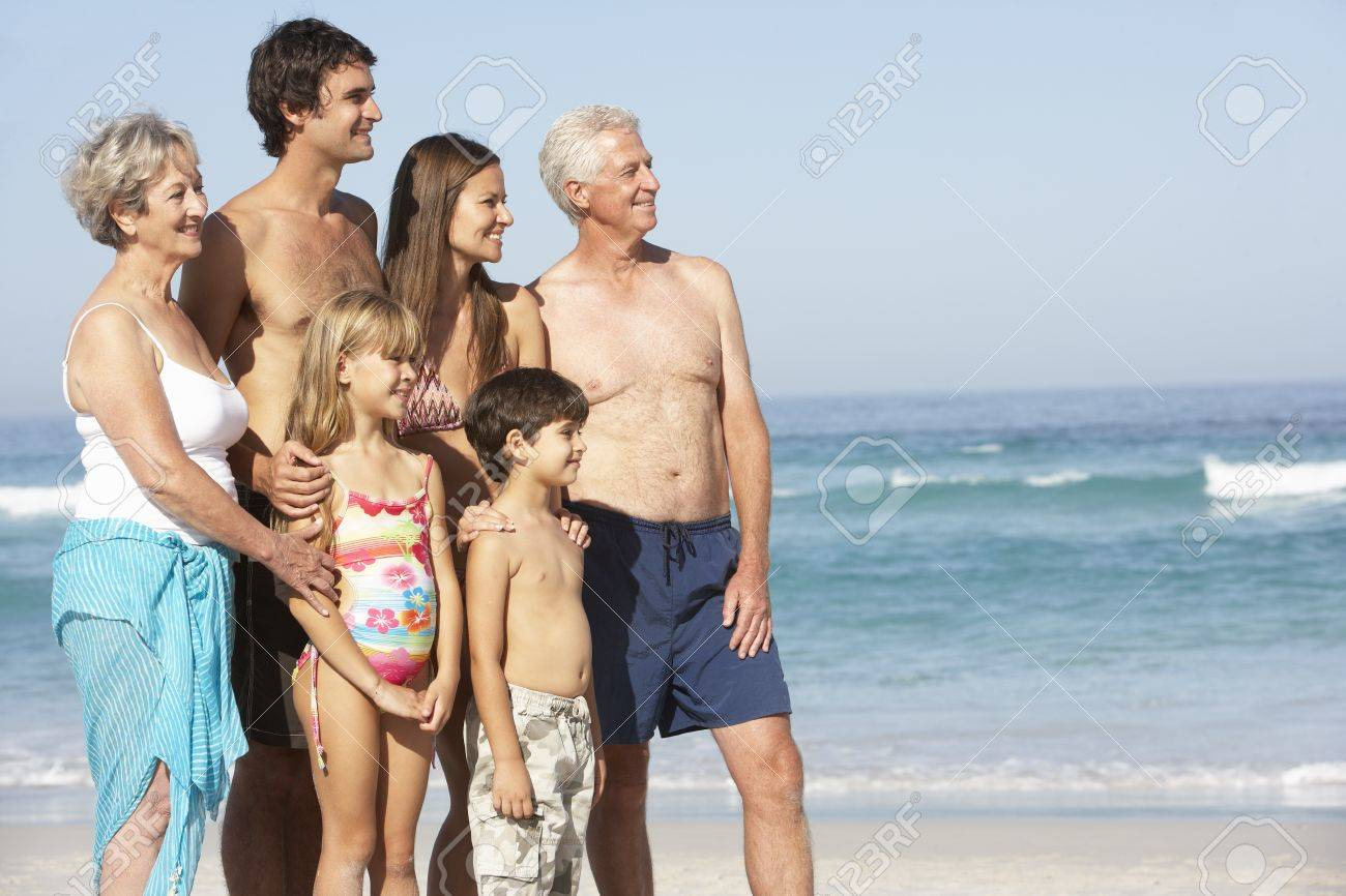 Three Generation Family On Holiday Walking Along Beach Stock Photo - 8483272