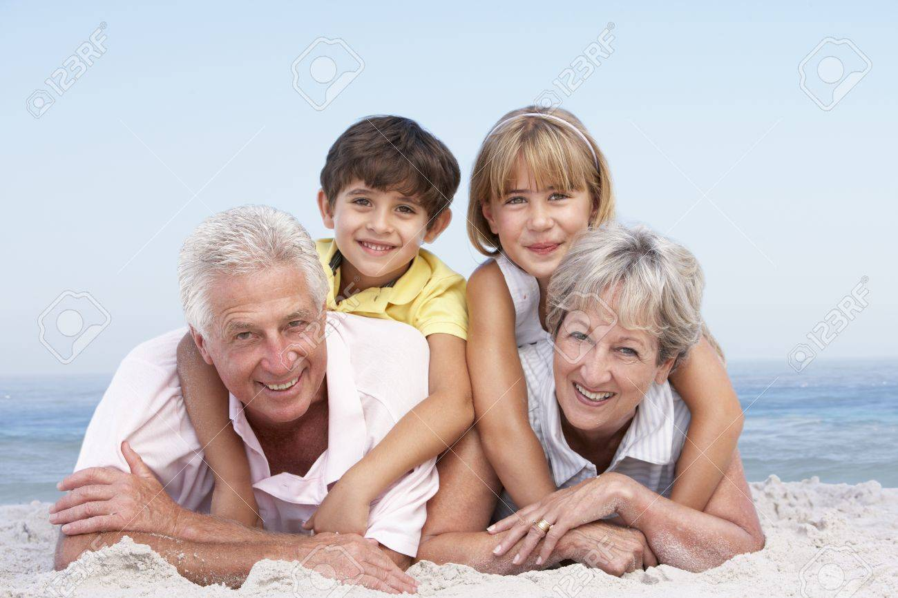 Grandparents And Grandchildren Relaxing On Beach Holiday Stock Photo - 8483170