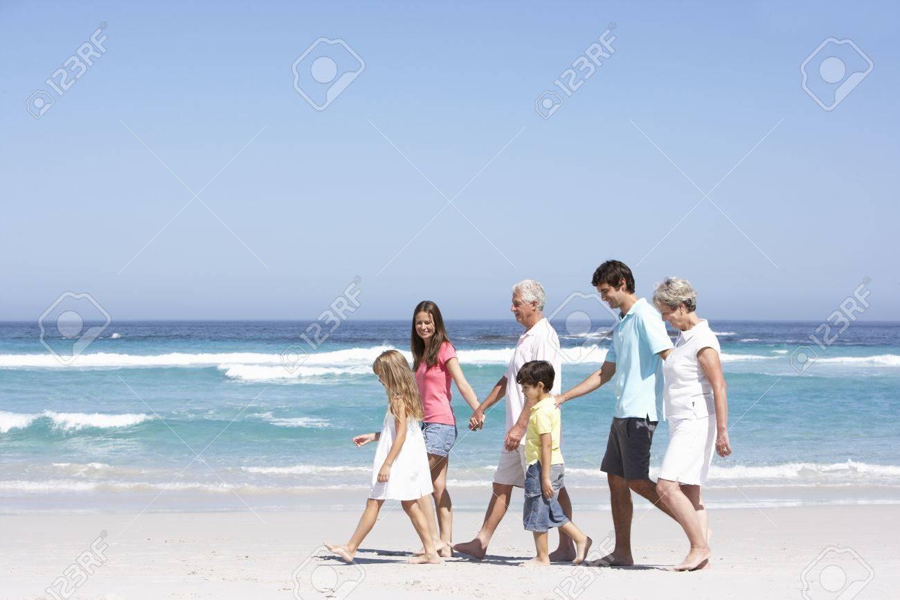 Three Generation Family Walking Along Sandy Beach Stock Photo - 8482944